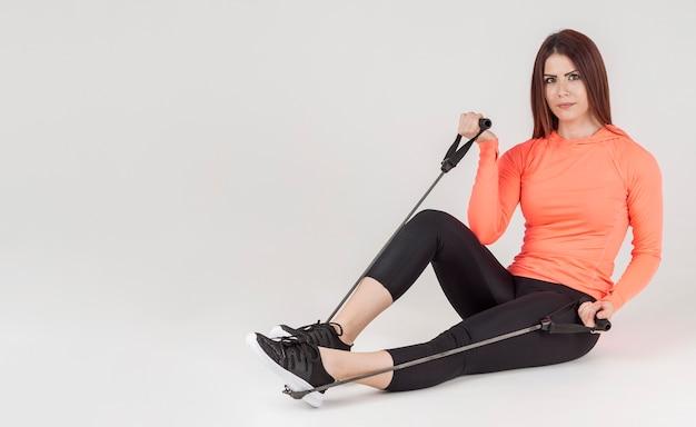 Vista lateral da mulher posando durante o exercício com banda de resistência