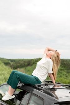 Vista lateral da mulher posando em cima do carro