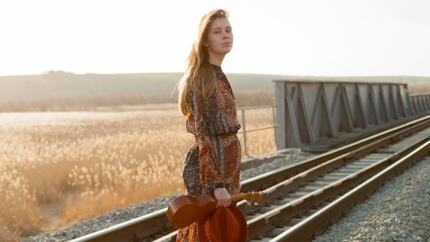 Vista lateral da mulher posando em trilhos de trem, mantendo o ukulele
