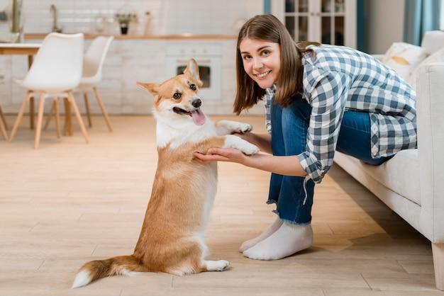 Vista lateral da mulher posando enquanto segura as patas do cão