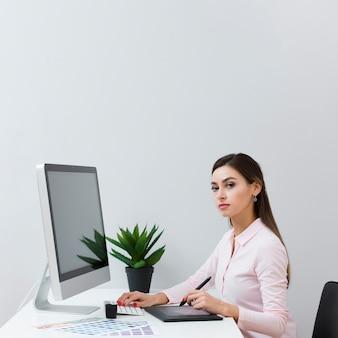 Vista lateral da mulher posando na mesa enquanto estiver usando o tablet