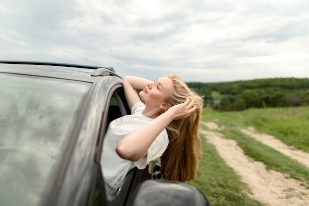 Vista lateral da mulher posando no carro