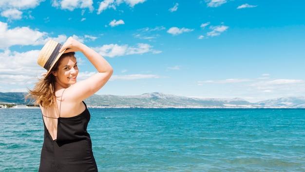 Vista lateral da mulher posando no oceano