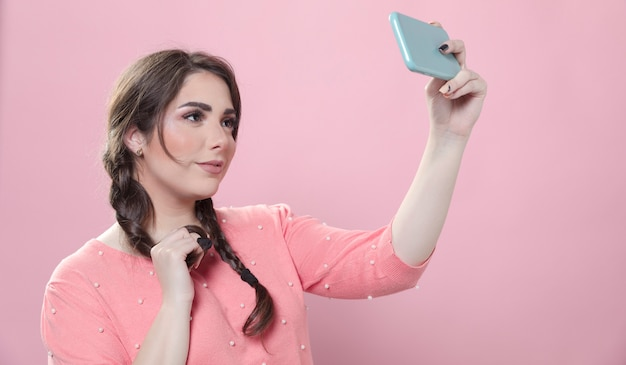 Vista lateral da mulher posando para uma selfie enquanto segura o smartphone