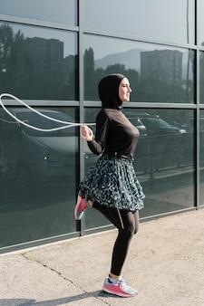 Vista lateral da mulher pulando corda
