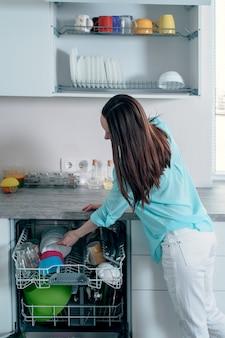 Vista lateral da mulher puxa pratos limpos da máquina de lavar louça