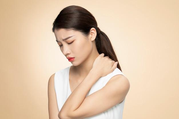 Vista lateral da mulher que sofre de dor de garganta, isolada em fundo laranja