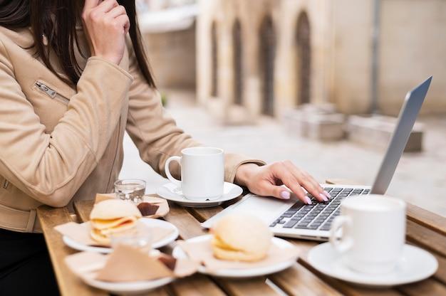 Vista lateral da mulher que trabalha ao ar livre e almoçar