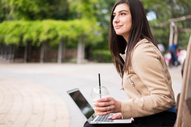 Vista lateral da mulher que trabalha ao ar livre no laptop