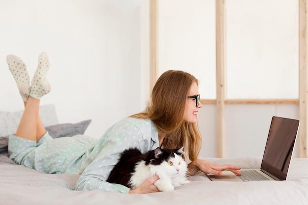 Vista lateral da mulher que trabalha de pijama de casa com gato