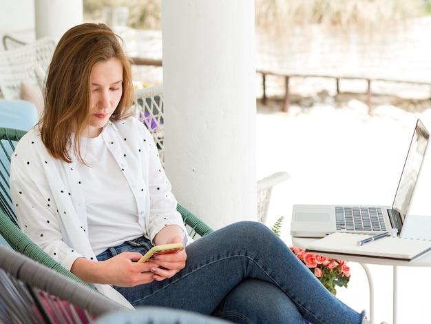 Vista lateral da mulher que trabalha fora com smartphone e laptop