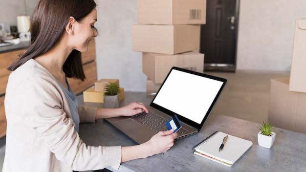 Vista lateral da mulher que trabalha na mesa, mantendo o cartão de crédito