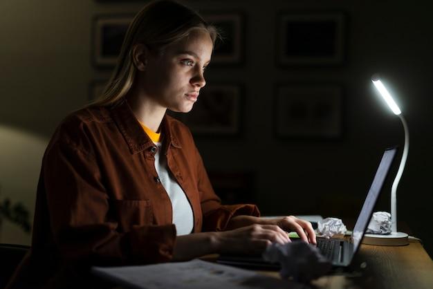 Vista lateral da mulher que trabalha na mesa