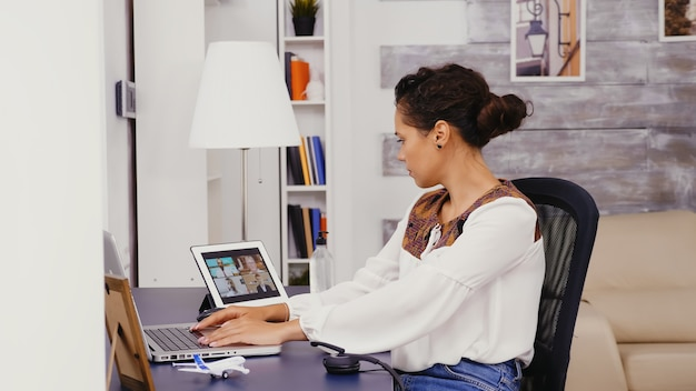 Vista lateral da mulher que trabalha no laptop em casa durante uma videochamada no computador tablet com colegas de trabalho.