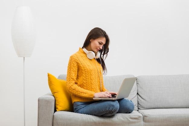 Vista lateral da mulher que trabalha no laptop no sofá dela