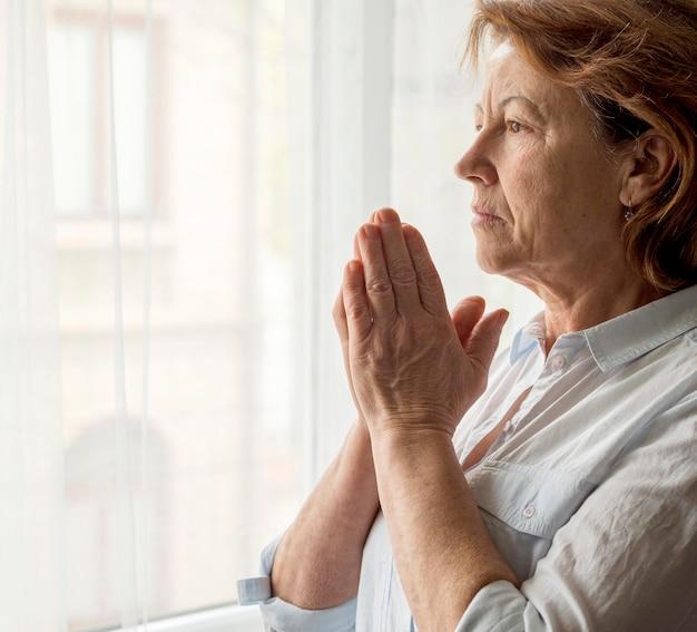 Vista lateral da mulher rezando