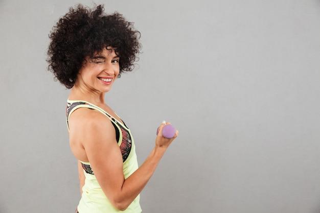 Vista lateral da mulher satisfeita fitness fazendo exercício com halteres