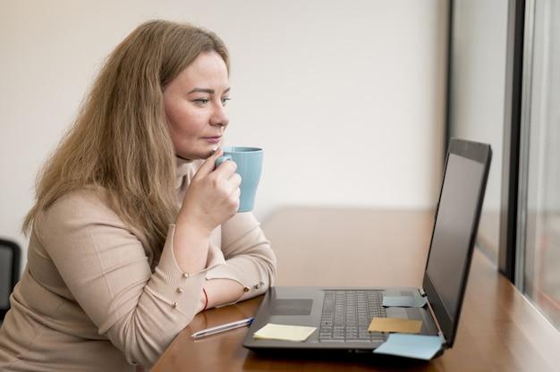 Vista lateral da mulher segurando a caneca e trabalhando no laptop no escritório