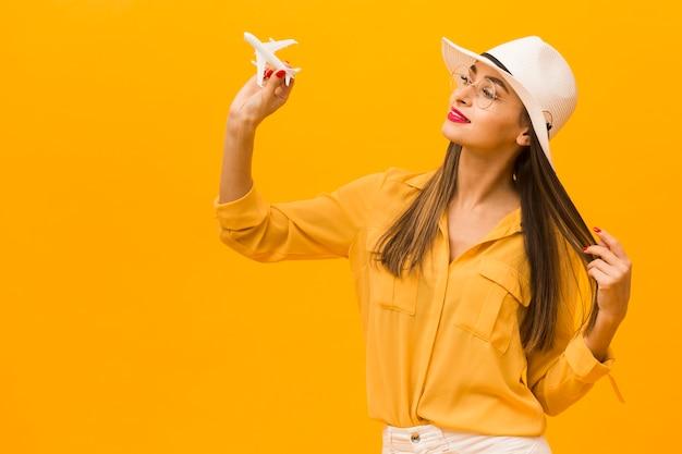 Vista lateral da mulher segurando a estatueta de avião com espaço de cópia