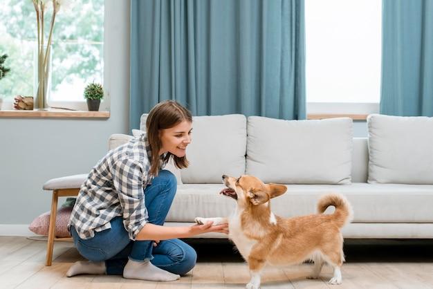 Vista lateral da mulher segurando a pata do seu cachorro em casa