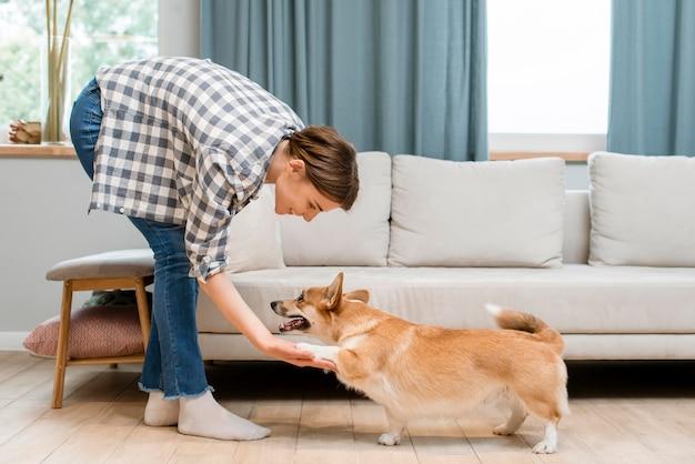 Vista lateral da mulher segurando a pata do seu cão