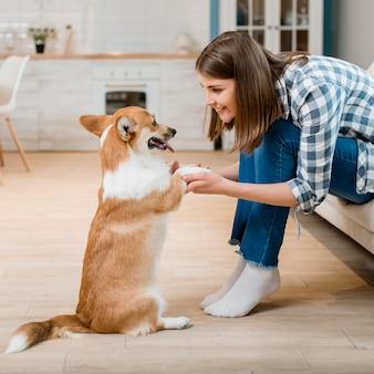 Vista lateral da mulher segurando as patas do seu cão