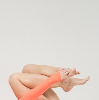 Vista lateral da mulher segurando as pernas com espaço de cópia