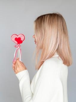 Vista lateral da mulher segurando coração