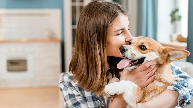 Vista lateral da mulher segurando e beijando seu cachorro