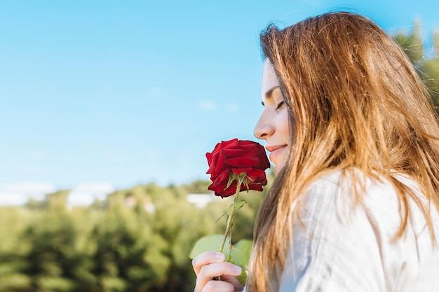 Vista lateral da mulher segurando e cheirando a rosa