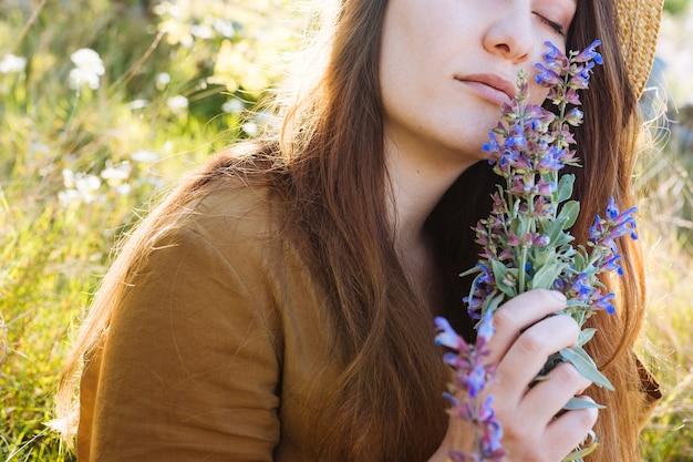 Vista lateral da mulher segurando e cheirando o buquê de flores