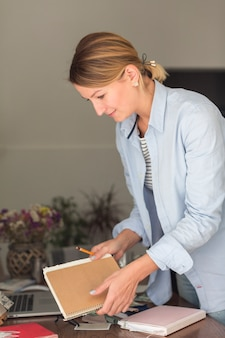 Vista lateral da mulher segurando o caderno e lápis