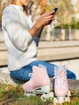 Vista lateral da mulher segurando o smartphone com patins
