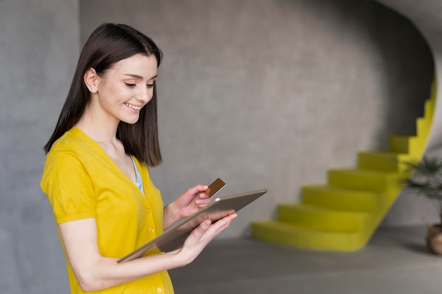 Vista lateral da mulher segurando o tablet e cartão de crédito
