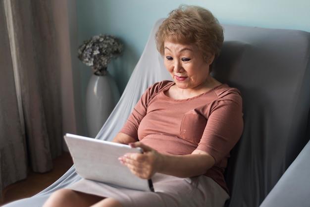 Vista lateral da mulher segurando o tablet