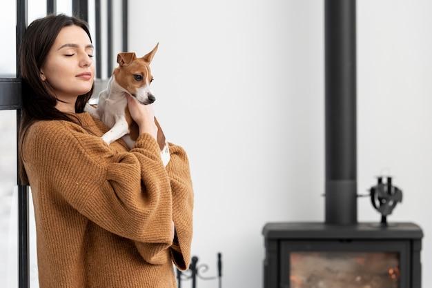 Vista lateral da mulher segurando seu cachorro