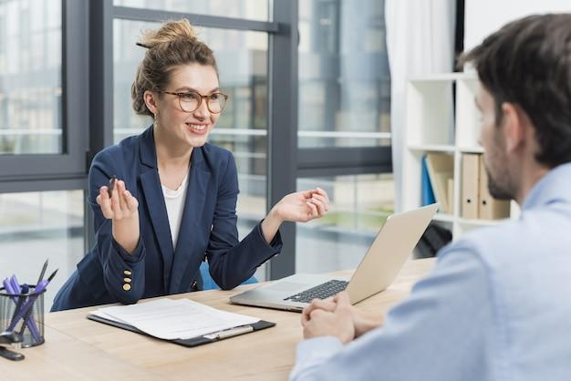 Vista lateral da mulher segurando uma entrevista de emprego com homem