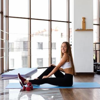 Vista lateral da mulher sentada no tapete de ioga