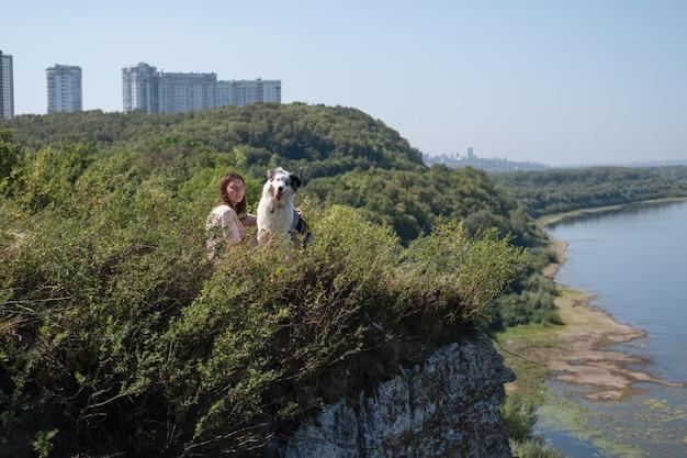 Vista lateral da mulher sente-se com o cão merle pastor australiano na margem do rio, verão. amor e amizade entre humanos e animais. viaje com animais de estimação.