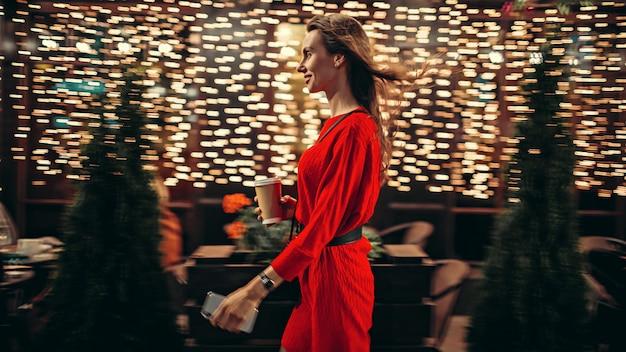 Vista lateral da mulher sorridente a pé na cidade à noite