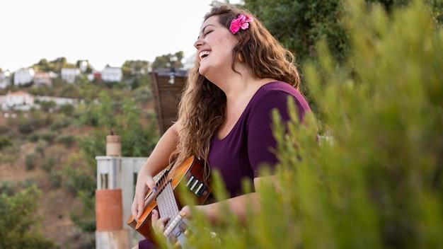 Vista lateral da mulher sorridente ao ar livre com guitarra