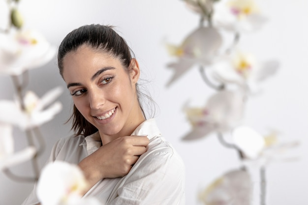 Vista lateral da mulher sorridente com orquídeas desfocadas