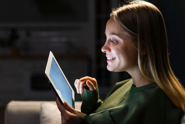 Vista lateral da mulher sorridente com tablet