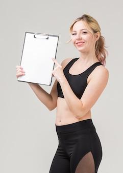 Vista lateral da mulher sorridente em athleisure segurando o bloco de notas
