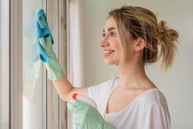 Vista lateral da mulher sorridente, limpando a janela