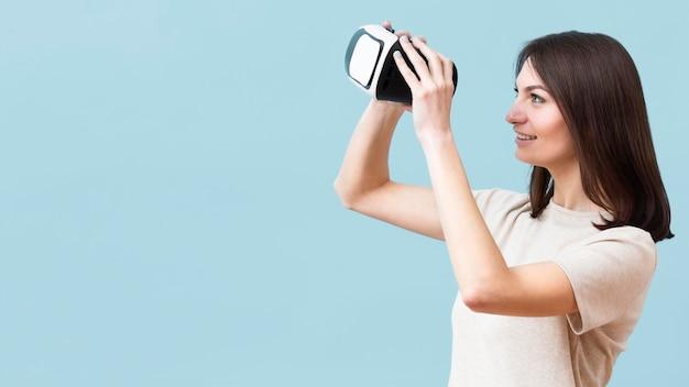 Vista lateral da mulher sorridente, olhando através do fone de ouvido da realidade virtual