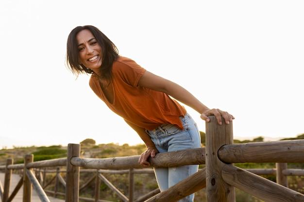 Vista lateral da mulher sorridente posando ao ar livre na natureza