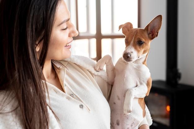 Vista lateral da mulher sorridente posando com seu cachorro