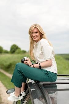 Vista lateral da mulher sorridente posando em cima do carro enquanto segura a câmera