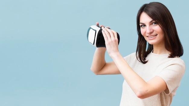 Vista lateral da mulher sorridente segurando fone de ouvido de realidade virtual